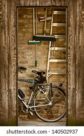 Retro styled image of a shed with a bicycle and garden tools inside