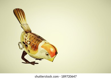 Retro styled image of a tin wind up toy bird on a vintage background
