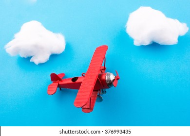 Retro styled little red model airplane in sky