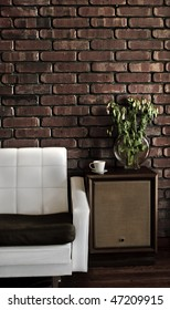 Retro styled lounge room showing a couch, speakers, cup, plant on wooden floor and a brick wall.