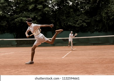 retro styled men playing tennis at court