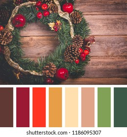Retro styled photo of a Christmas wreath, with ribbons, fir cones, apples and berries, over old wood background. In a colour palette with complimentary colour swatches.