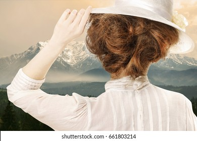 Retro styled picture of woman in victorian hat looking at the high mountains with snow on peaks. Sepia filter.