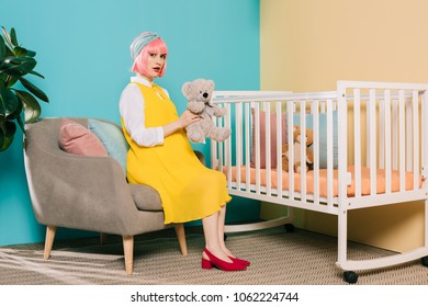 retro styled pregnant pin up woman with pink hair sitting with teddy bear near baby cot in child room