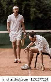 retro styled tennis player putting ball on ground at tennis court
