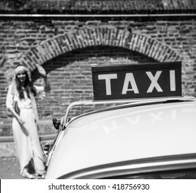 Retro styled woman hail a vintage taxi. Closeup on the taxi sign.