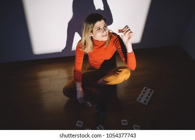 Retro styled woman looking at photo slides in front of projector screen