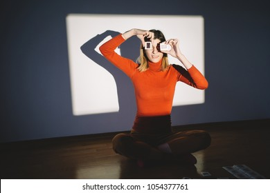 Retro styled woman looking through photo slides in front of projector screen