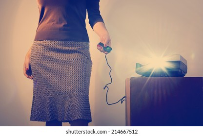 Retro styled woman operating a slide projector with a wired remote control and lens flare from projector light