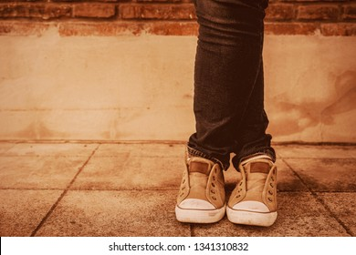 Retro style,Shapely female cross one's legs  in sneakers and jeans near a concrete wall