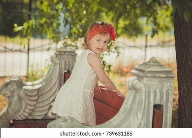 Retro stylish dressed blond young baby girl child posing in central park garden wearing french couturer white dress red bandana and chaplet.