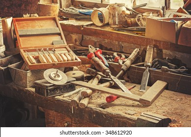 Retro stylized old tools on wooden table in a joinery.