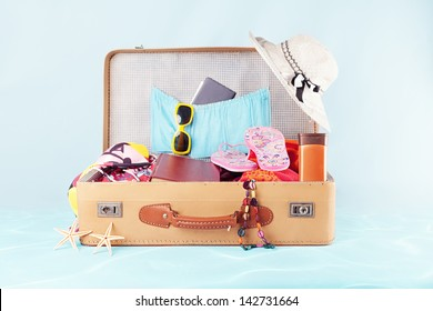 retro suitcase with full of clothes,books and passport on blue background