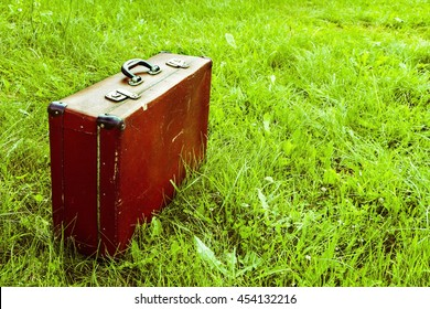 Retro suitcase stands on green grass. Travel, trips, memories. - Shutterstock ID 454132216