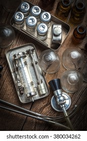 Retro syringe, stethoscope and medical cupping glass on a wooden table.