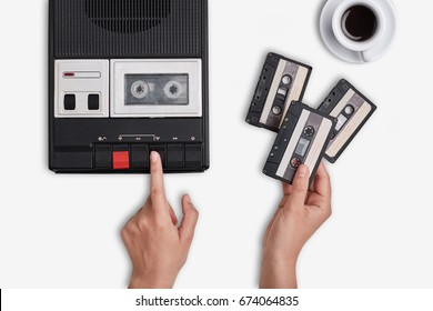 Retro tape recorder, cassettes and cup of hot coffee standing on white surface. Hands switching on cassette tape recorder changing cassettes. Top flat view of old devices. Tape recorder from 80s