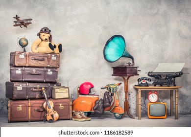 Retro Teddy Bären Spielzeug in Aviator's Hut, hölzernes Flugzeug, gealterte klassische Reise-Täler, Globus, Kinder Pedal-Roller, Phonograph, Schreibmaschine, Uhr, TV, Radio, altes Telefon. Vintage-gefiltertes Foto