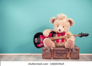 Retro Teddy Bear toy with hairstyle playing bass guitar and sitting on old leather travel luggage. Hard rock or heavy metal music concept. Vintage nostalgia style filtered photo