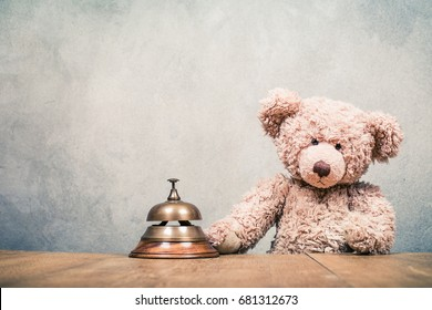 Retro Teddy Bear toy with hotel reception service desk bell front concrete wall background. Vintage instagram style filtered photo