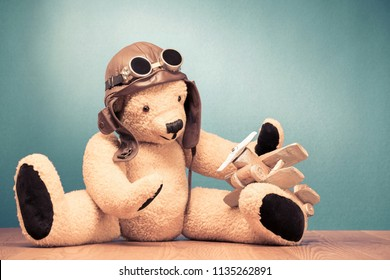 Retro Teddy Bear toy in leather pilot's hat and vintage goggles sitting on the floor and playing with handmade wooden plane front mint green wall background. Old style filtered photo