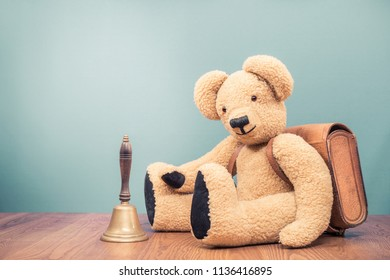 Retro Teddy Bear toy with leather school bag and old bronze bell front mint green wall background. Vintage style filtered photo