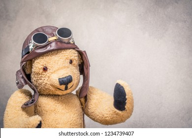 Retro Teddy Bear toy in leather pilot's helmet with aviator goggles front textured concrete wall background. Vintage old style filtered photo