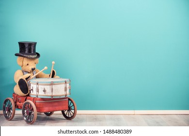 Retro Teddy Bear toy in old cylinder hat sitting on old luggage with wheels and playing the drum front mint blue wall background. Music concept. Vintage nostalgia style filtered photo