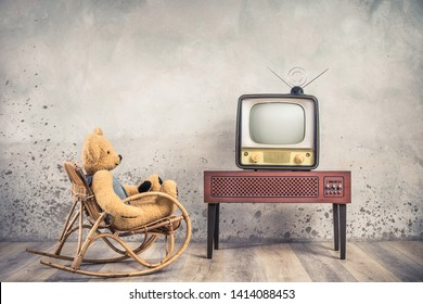 Retro Teddy Bear toy on rocking chair watching old outdated analog television receiver from 50s on wooden TV stand front aged loft textured concrete wall background. Vintage style filtered photo