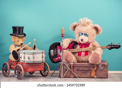 Retro Teddy Bear toy play bass guitar and sitting on old luggage, golden microphone and Teddy Bear in cylinder hat playing the drum. Rock or metal music concept. Vintage nostalgia style filtered photo