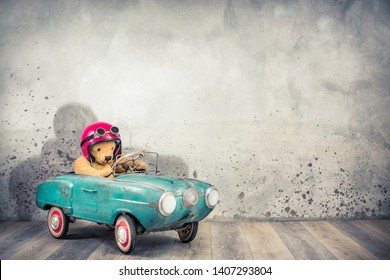 Retro Teddy Bear toy racer in old helmet hat with aviator goggles driving antique rusty turquoise pedal car from 60s front concrete wall background with shadow concept. Vintage style filtered photo