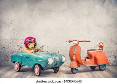 Retro Teddy Bear toy racer in old helmet hat with goggles driving antique rusty mint blue pedal car from 60s and orange kids scooter trike front concrete wall background. Vintage style filtered photo