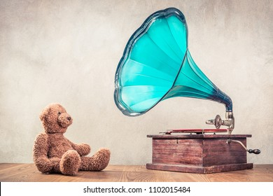 Retro Teddy Bear toy sitting near antique classic old gramophone turntable player on oak wooden floor front concrete wall background. Listening to music concept. Vintage instagram style filtered photo