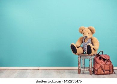 Retro Teddy Bear toy sitting on aged wooden stool and old leather school bag backpack for books front mint blue wall background. Vintage style filtered photo