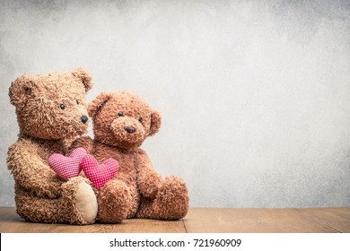 Retro Teddy Bear toys pair with handmade Valentines day love hearts front concrete wall background. Vintage instagram old style filtered photo