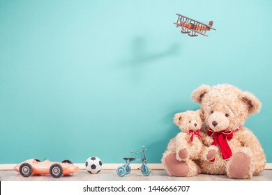 Retro Teddy Bears, old toy trike bicycle, obsolete plastic car, soccer ball, flying wooden plane front aquamarine wall background. Mother or father with baby concept. Vintage style filtered photo