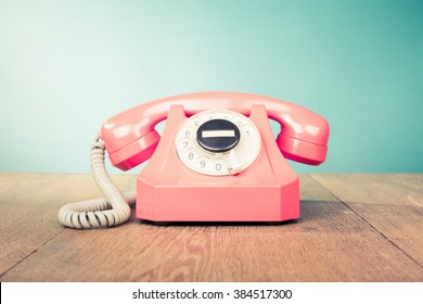 Retro telephone front mint green wall background. Old style filtered photo