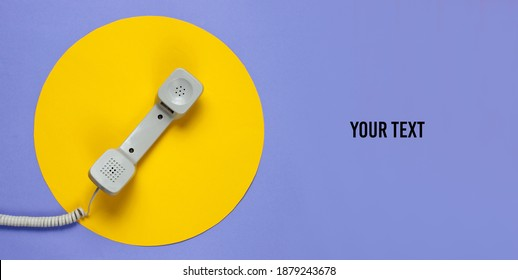 Retro telephone handset on a purple background with a yellow circle and space for your text. Pop culture. 80s. Minimalistic fashion shot. Top view