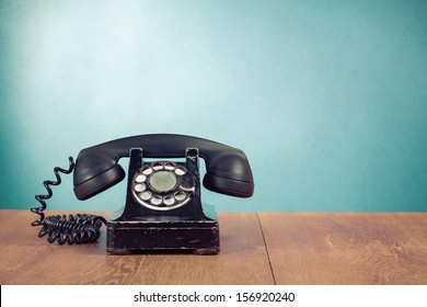 Retro telephone on table in front mint green background