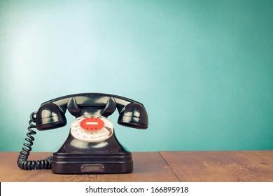 Retro telephone on table front aquamarine background