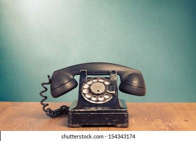 Retro telephone on wood table for old style background