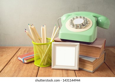Retro telephone, pencils, frame and old books on wooden table