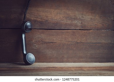 retro telephone receiver on wooden board with copy space