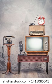 Retro television from 50s, old microphone, radio receiver, orange alarm clock on wooden TV stand and outdated telephone front aged textured concrete wall background. Vintage style filtered photo
