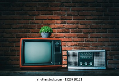 Retro television with old radio on wood table in old brick wall. Vintage style photo.