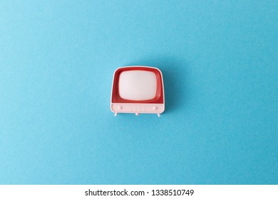 A retro television toy right in the middle of a pastel blue background