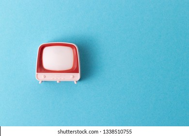 A retro television toy showing on a pastel blue background with a plenty of negative space