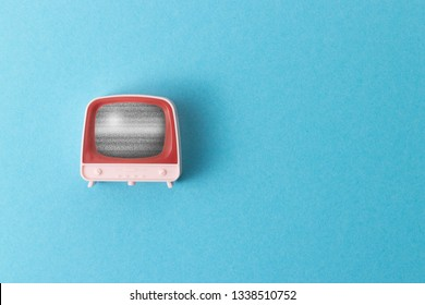 A retro television toy showing static tv noise on a pastel blue background with a plenty of negative space
