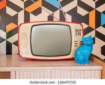 Retro television with vintage wallpaper in the background. Interior decoration ceramic figure from the 70s