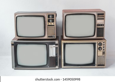 Retro televisions pile on floor in white room. vintage old tv style