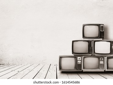 Retro televisions pile on floor in old room with white wall. Antique and vintage home decoration style. monochrome sepia photo.